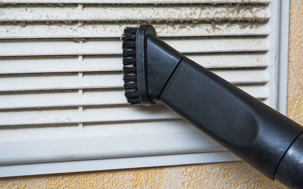 A person vacuuming the grille cover on an air vent.