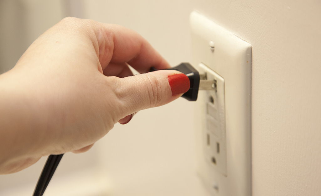 A person plugging into an outlet.
