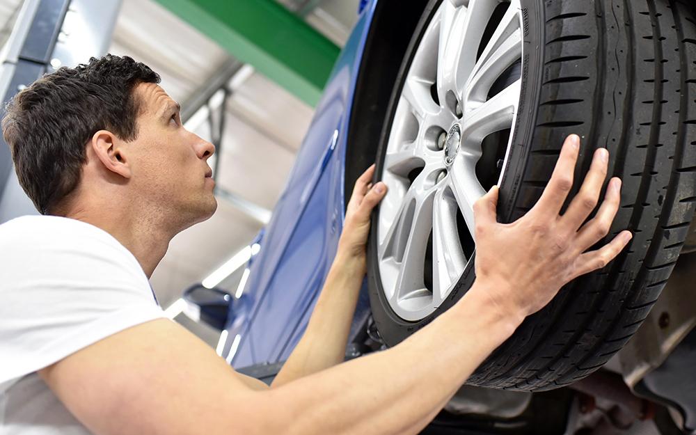 Một người đàn ông lắp lốp xe ô tô
