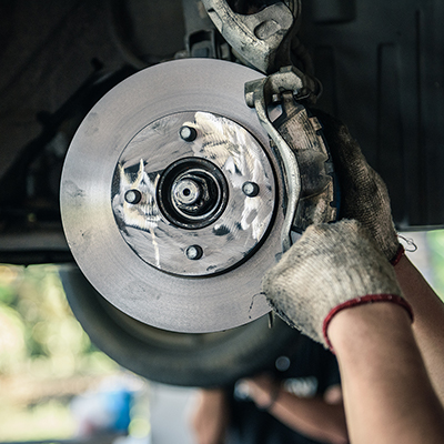 A person changing brake pads