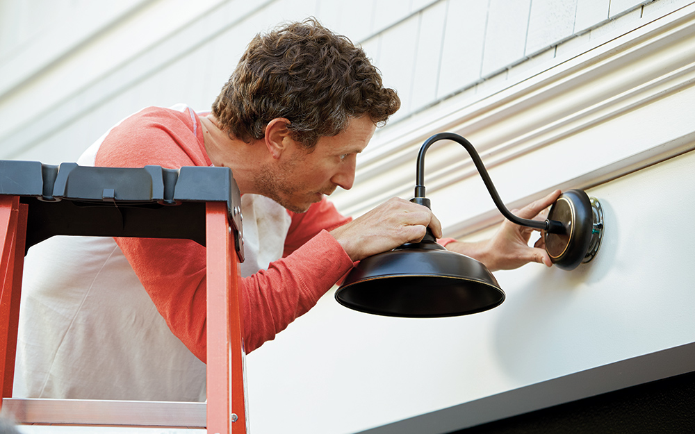 A man removing an outdoor sconce on a home