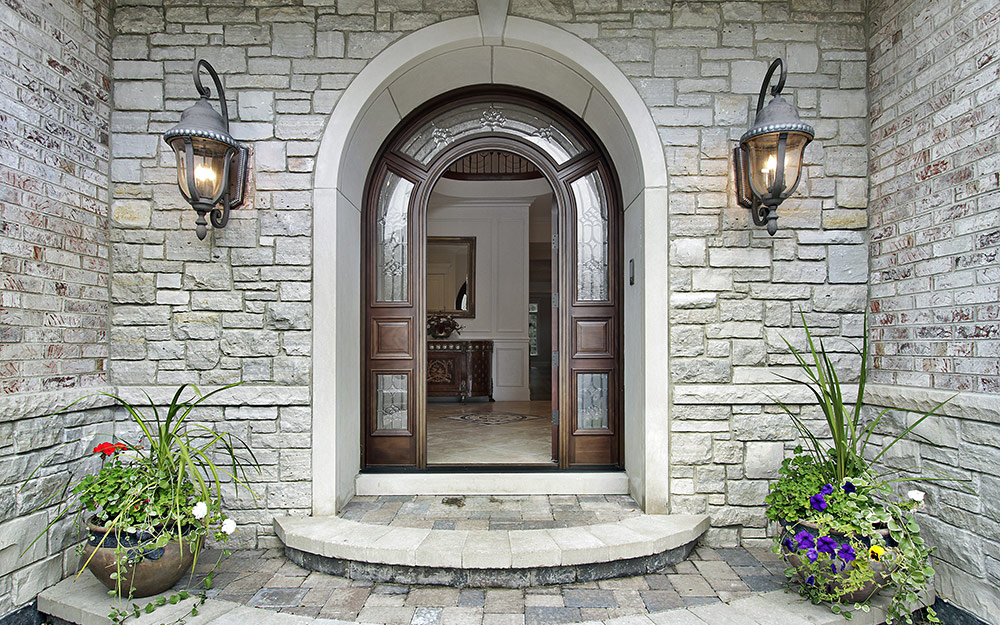 A stone exterior of a home with mounted lanterns