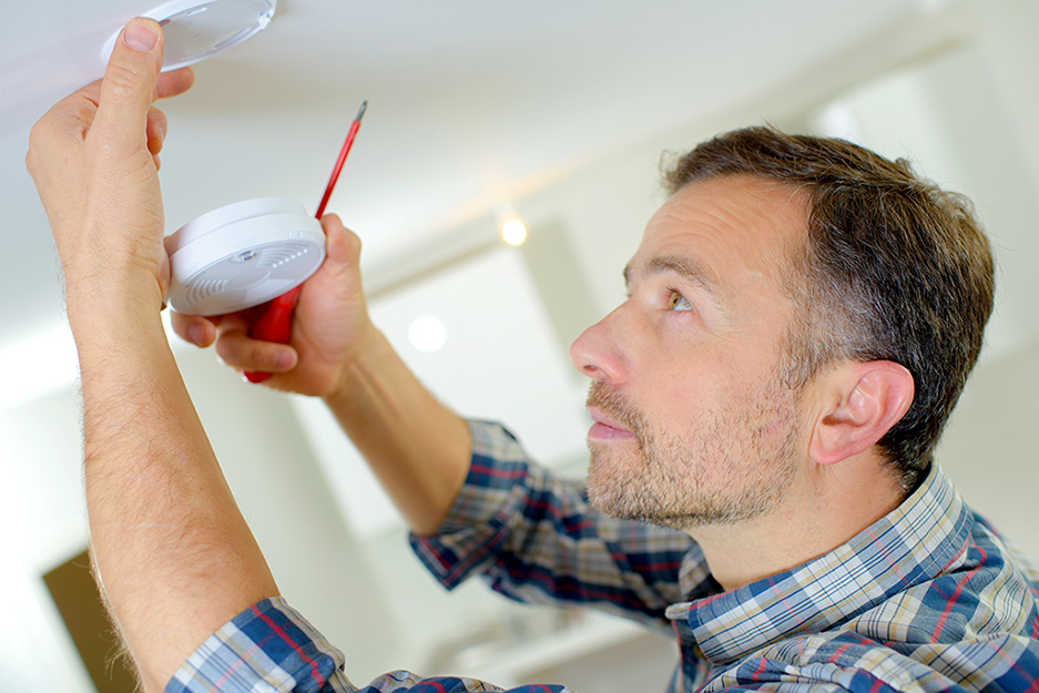 A man removing a smoke alarm from the ceiling.