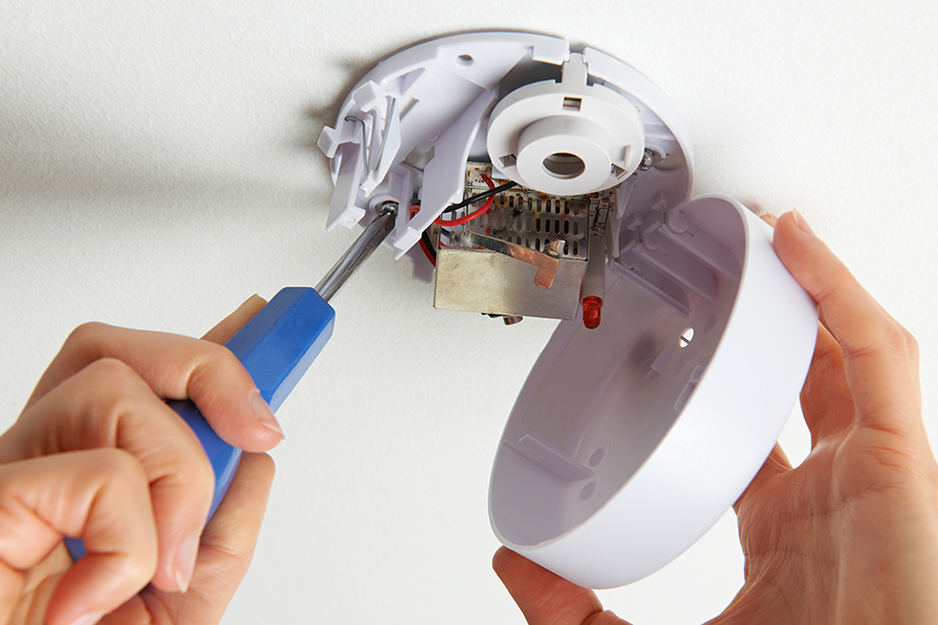 Someone opening a smoke alarm with a screwdriver.