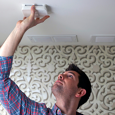 Man opening smoke alarm in ceiling.