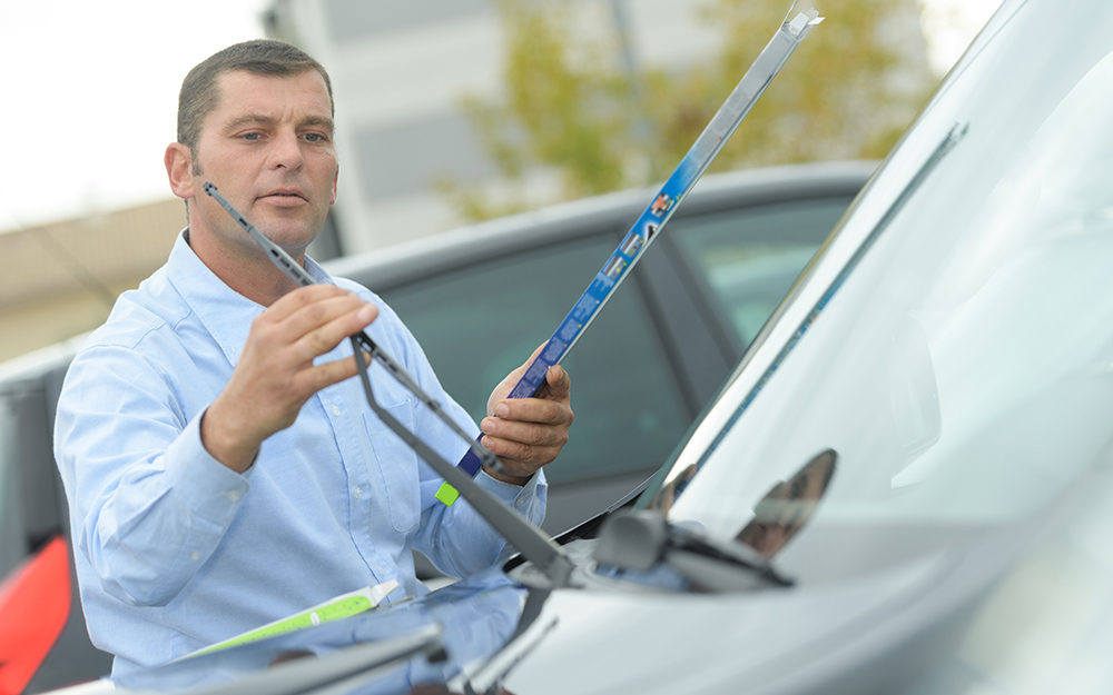 Man removing windshield wiper from package.