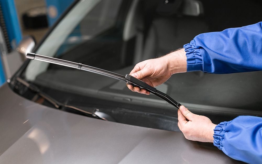 Person aligning wiper blade with tabs.