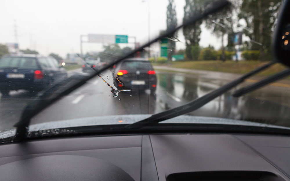 New windshield wiper blades clearing the rain from a windshield.