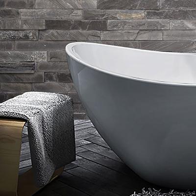 A gray bathtub sitting stone tiled bathroom