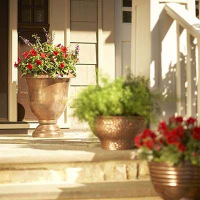 Planters filled with flowers sitting on a sunny porch.