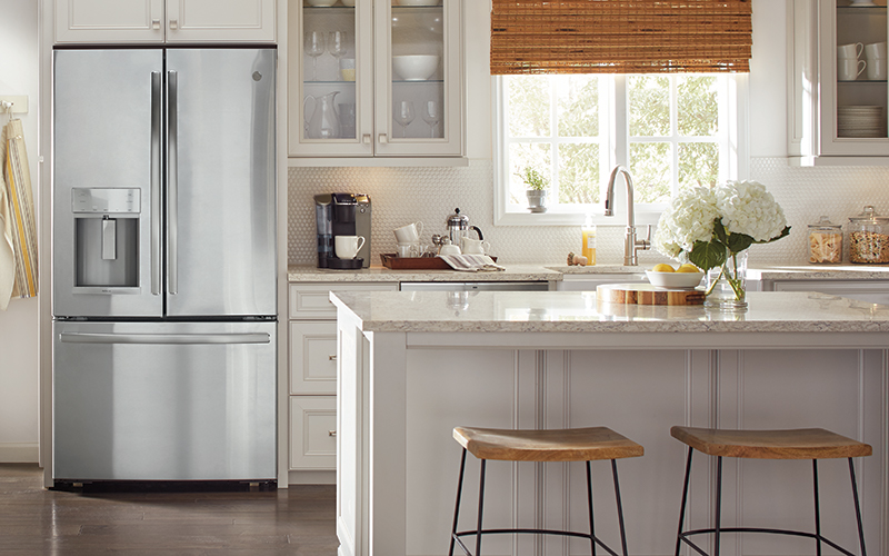 A stainless steel French door refrigerator stands in a white kitchen with an island.