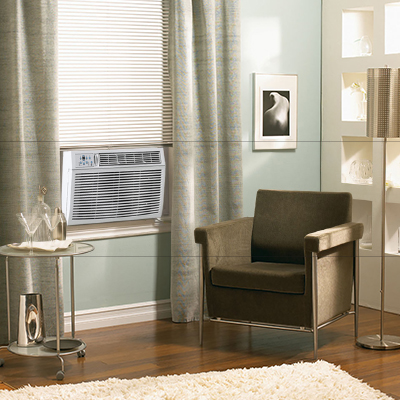 Window air conditioner next to a living room chair