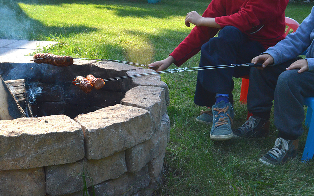 People roasting marshmallows around a fire pit