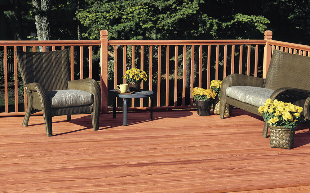 A deck made of redwood boards and railings provides ample space for outdoor seating.