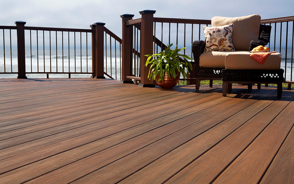 A deck built of composite or synthetic boards looks out over the ocean.
