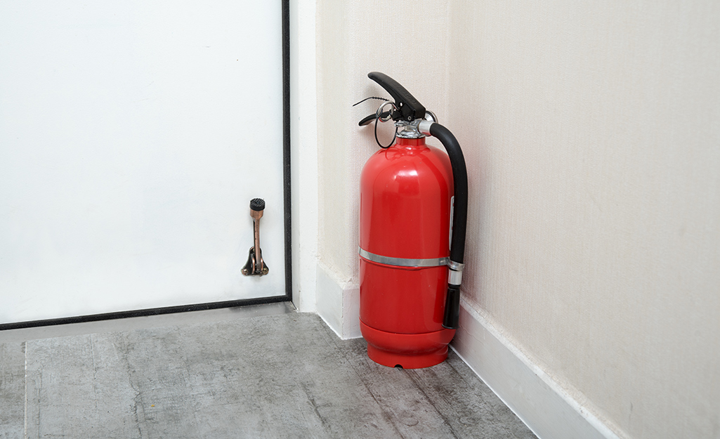 A fire extinguisher placed on the floor next to a doorway.