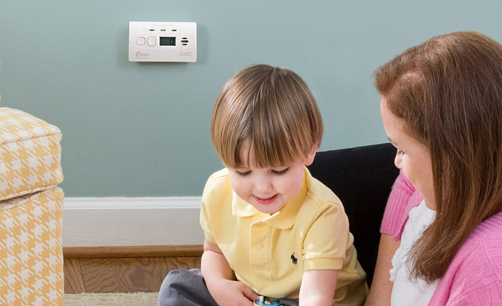 An adult playing with a child near a carbon monoxide alarm installed nearby.