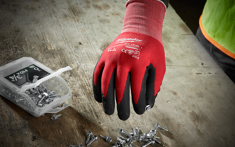 gloved hand holding a screw