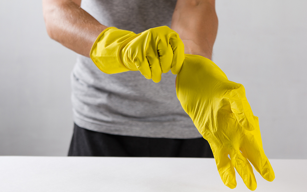 person pulling on protective yellow gloves