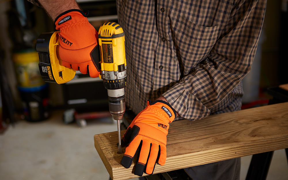 person wearing gloves while using a drill