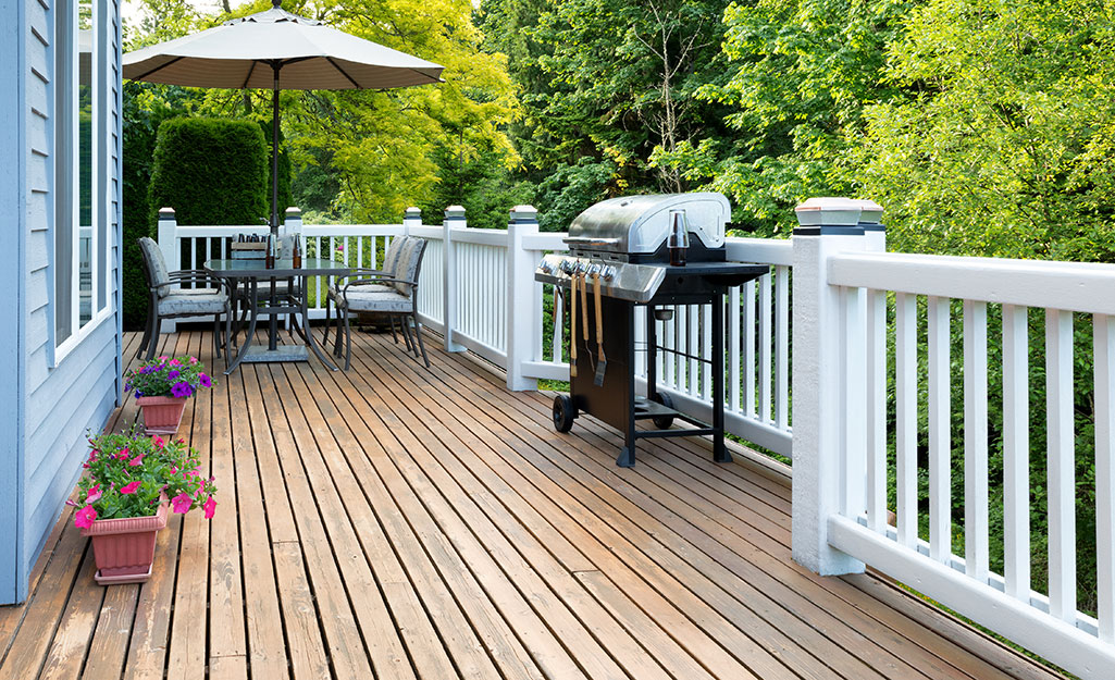 A stained deck surrounded by white railing.