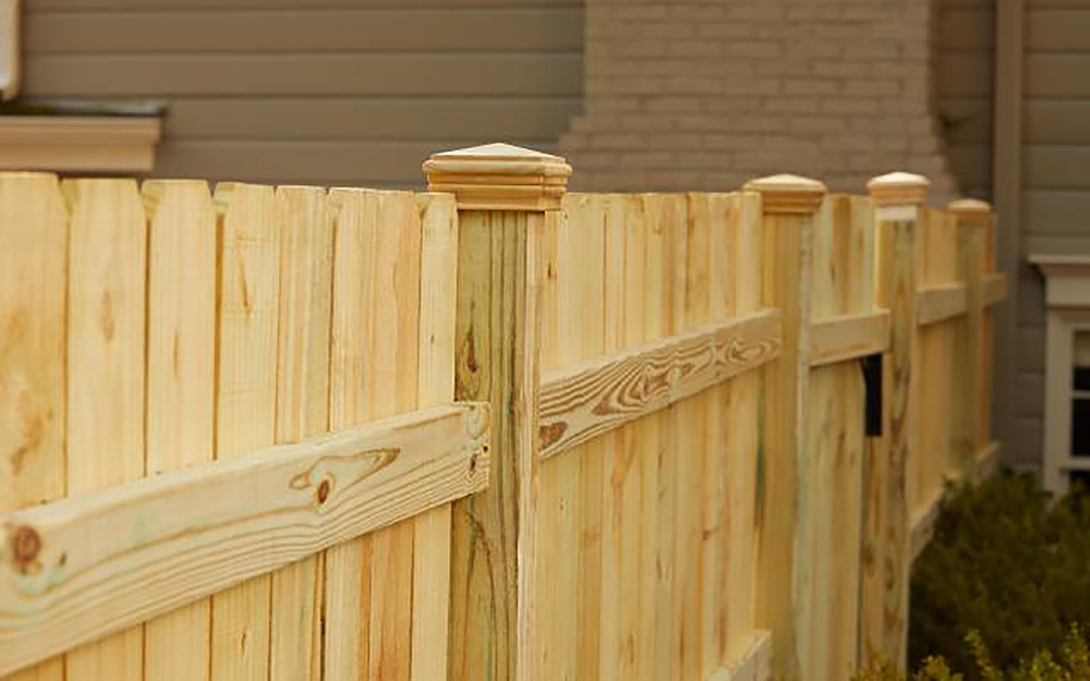 A new fence stands outside of a home.