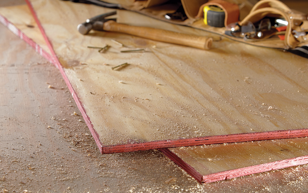 Two sheets of plywood lying on a concrete floor.