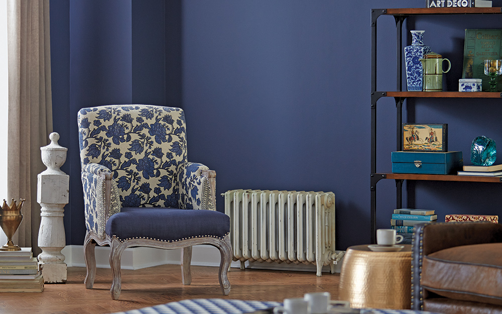 A blue and white floral print chair against a dark blue satin finish wall.