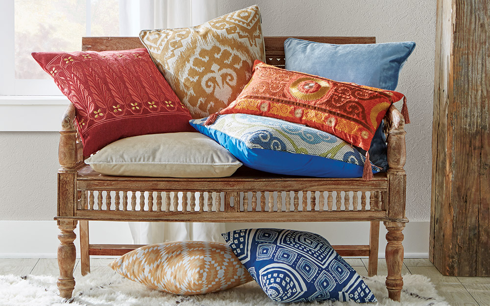 A hand-carved wood settee stacked high with orange, blue and tan pillows.