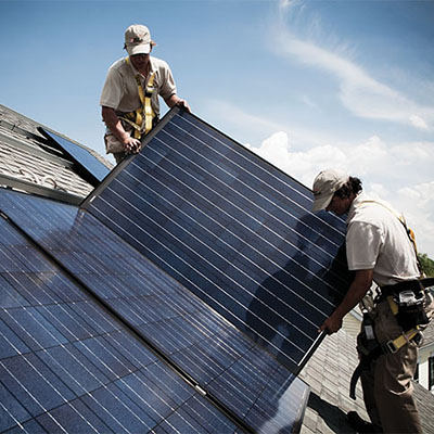 Two professional installers adding solar panels to a roof.