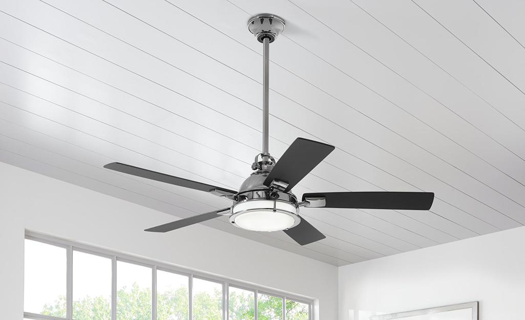 Fan installed on a white shiplap ceiling.