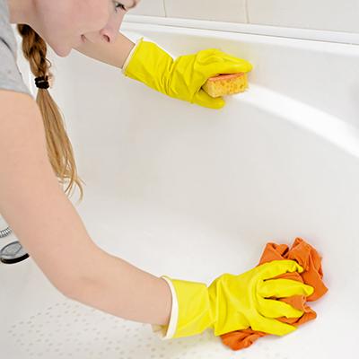 washing a bathtub with a rag