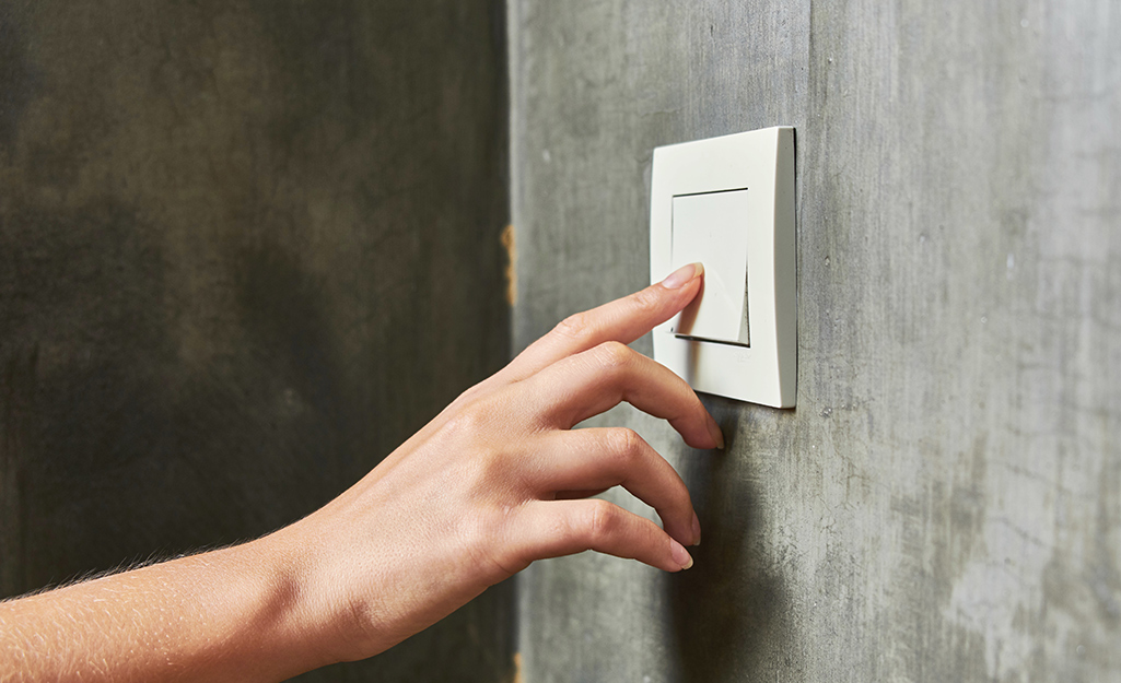 A person turning off a light switch.