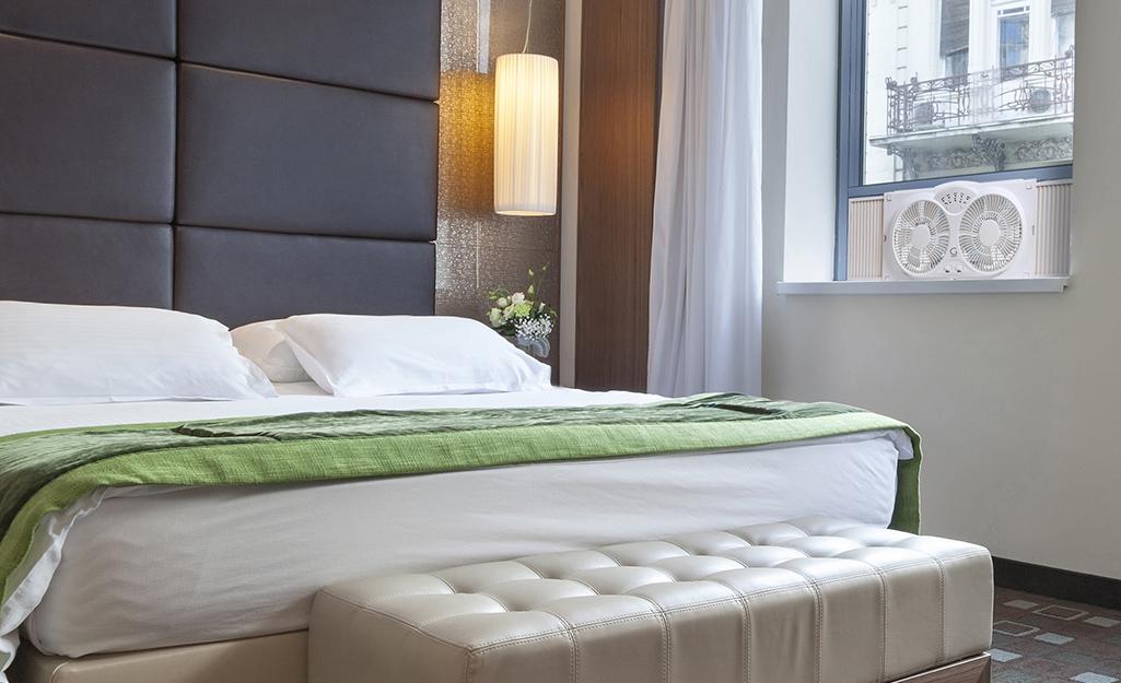 A bedroom with a window fan in the window.