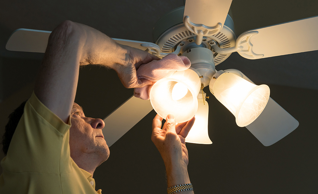 A person wiping dust off the globe of a ceiling fan.