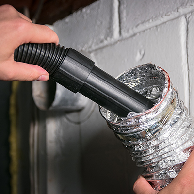 A person uses a vacuum hose attachment to clean inside a clothes dryer vent.