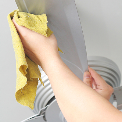A person uses a cloth to clean the blades of a ceiling fan.