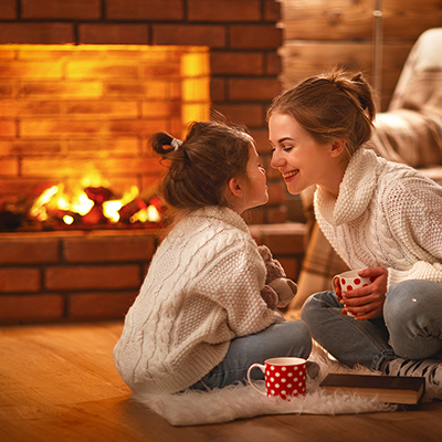 Mom and daughter drinking cocoa near a lit fireplace.