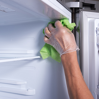 A person wears a glove to clean a freezer with a cloth.