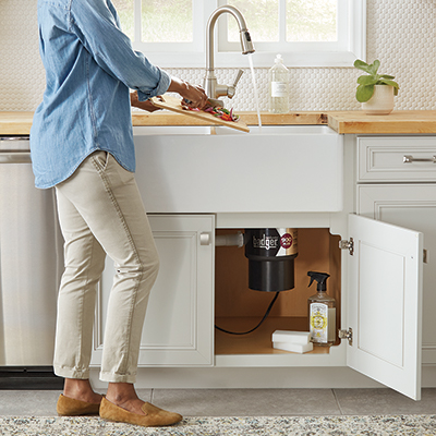 A person at a kitchen sink preparing to use a garbage disposal
