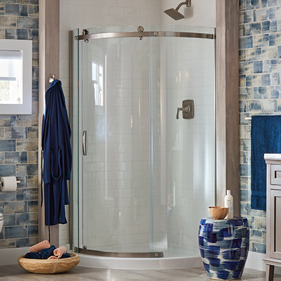 A glass shower door is featured in bathroom with wall tile