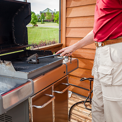 A man cleaning an open grill.