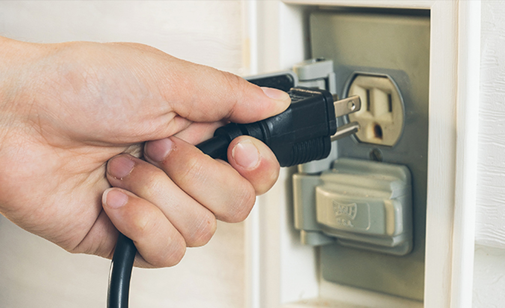 A man unplugs a power cord from an electrical outlet.