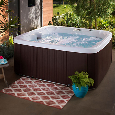 A sparkling clean hot tub sits on a patio.