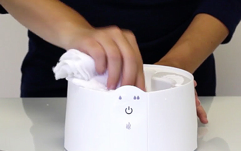 A person cleaning the inside of a humidifier.