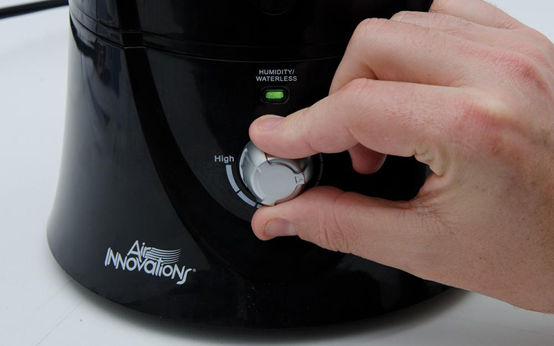 A person turning off a humidifier.