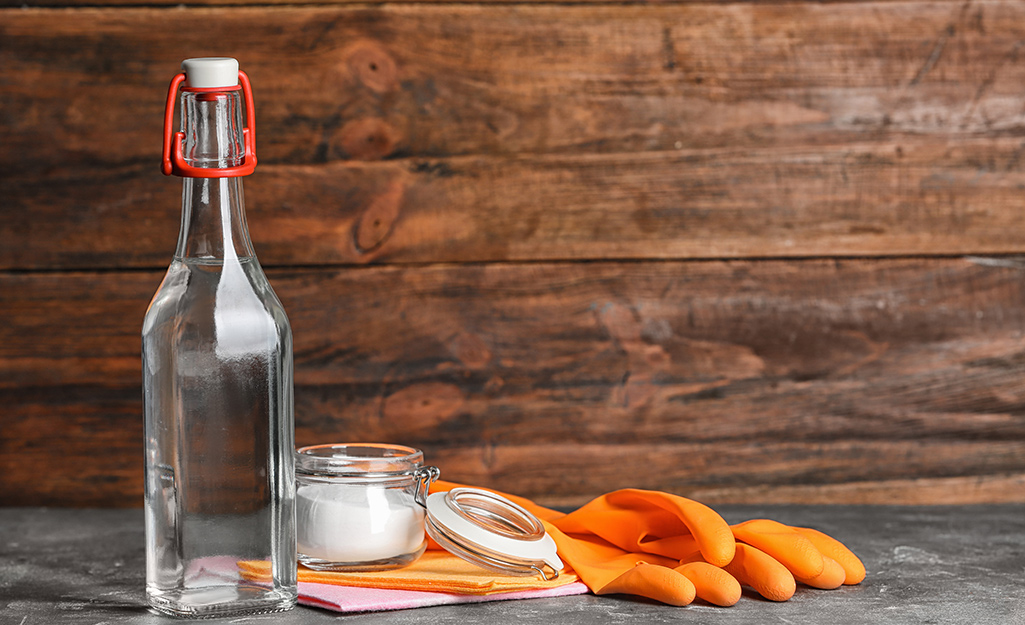 A glass bottle, baking soda and gloves on a table.