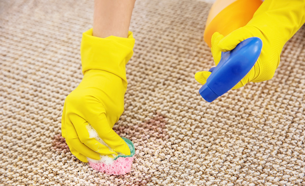 A person spot cleaning a jute rug.