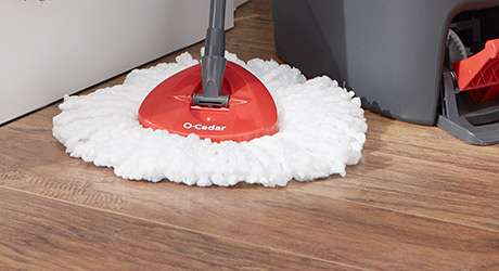 Cedar mop being used to clean a wood-look laminate floor.