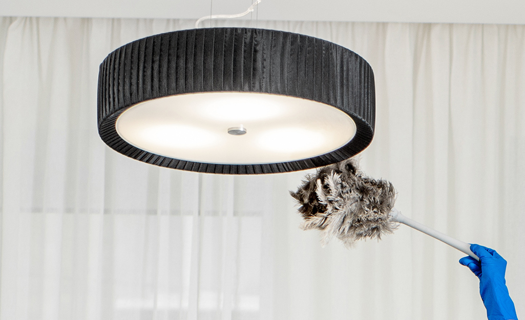 A duster being used on an overhead lamp shade.